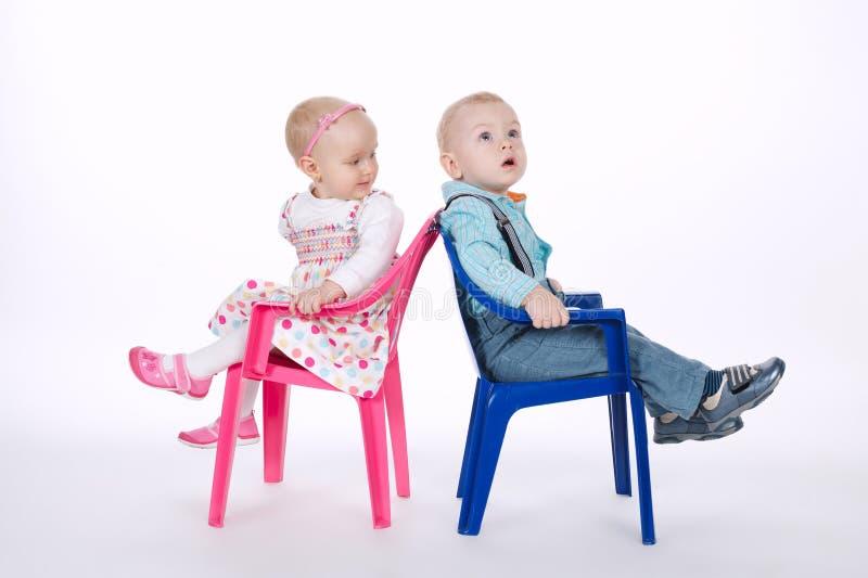 滑稽的男孩和女孩紧接坐椅子 免版税库存图片