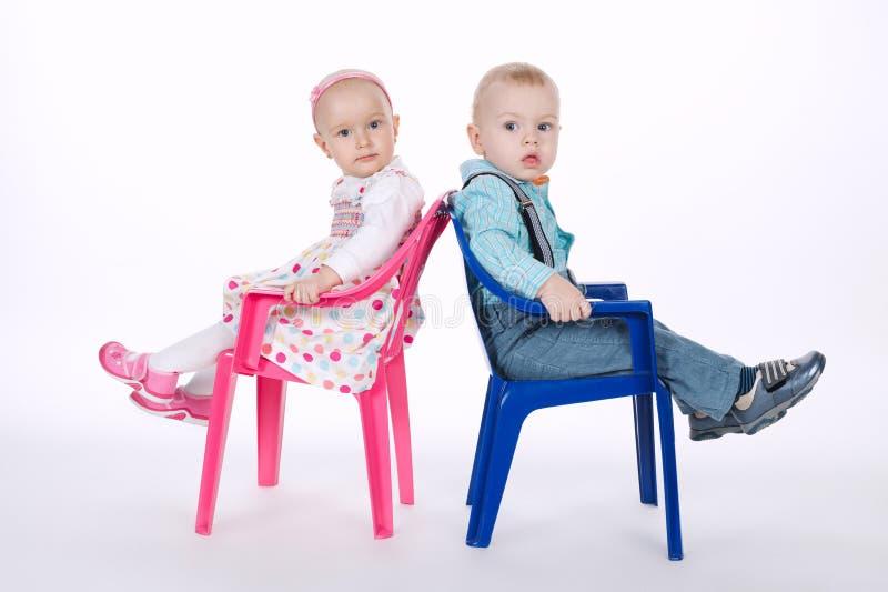 滑稽的男孩和女孩紧接坐椅子 免版税图库摄影