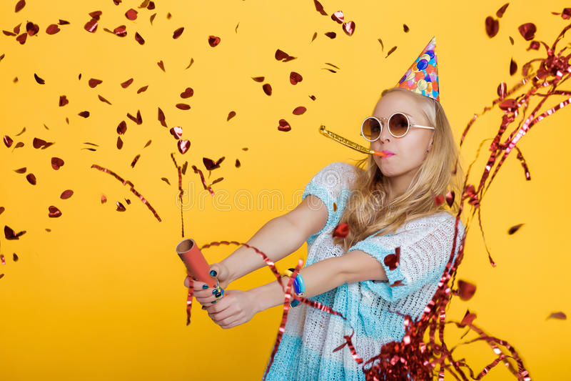 滑稽的白肤金发的妇女和在黄色背景的红色五彩纸屑画象生日帽子的 庆祝和党 免版税库存照片