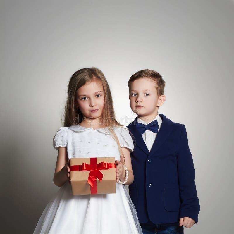 滑稽的美好的加上在箱子的一件礼物 一起秀丽小女孩和男孩 库存图片