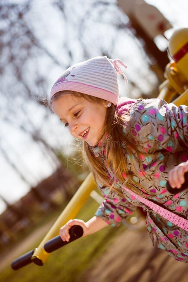滑稽的逗人喜爱的白肤金发的小女孩获得乘坐摇摆的乐趣看拷贝空间&愉快微笑在春天或秋天公园 库存图片