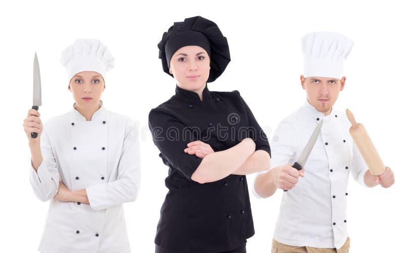 滑稽的年轻人和两名妇女在白色隔绝的厨师制服的 库存照片