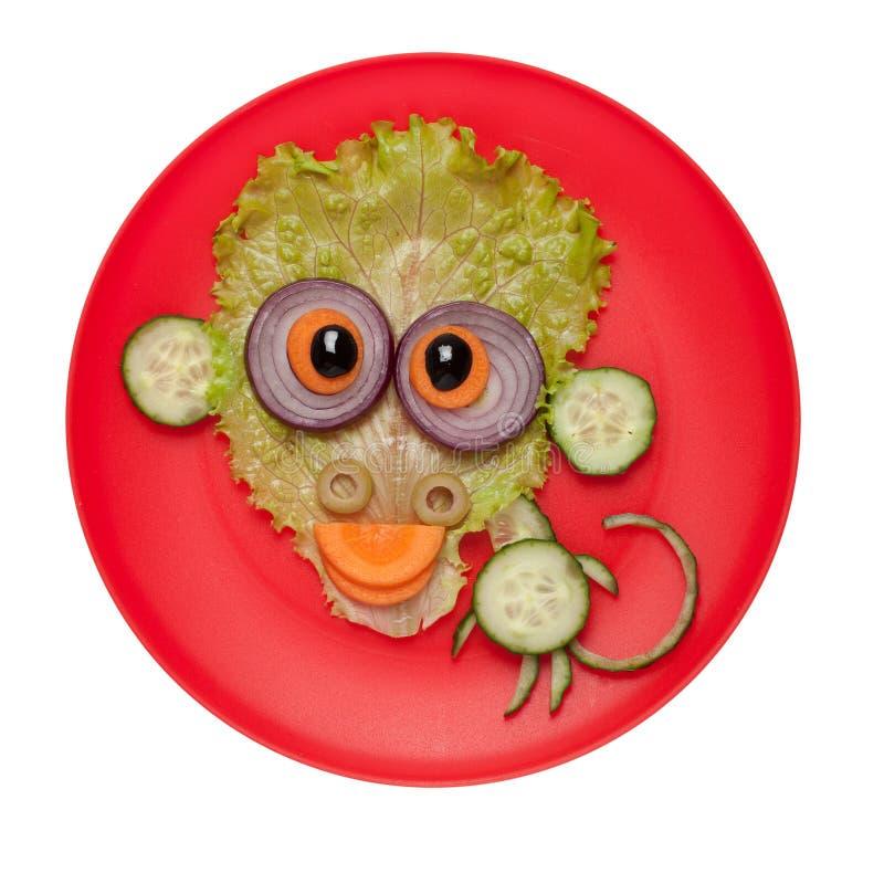 滑稽的猴子由黄瓜和沙拉制成在板材 免版税库存图片