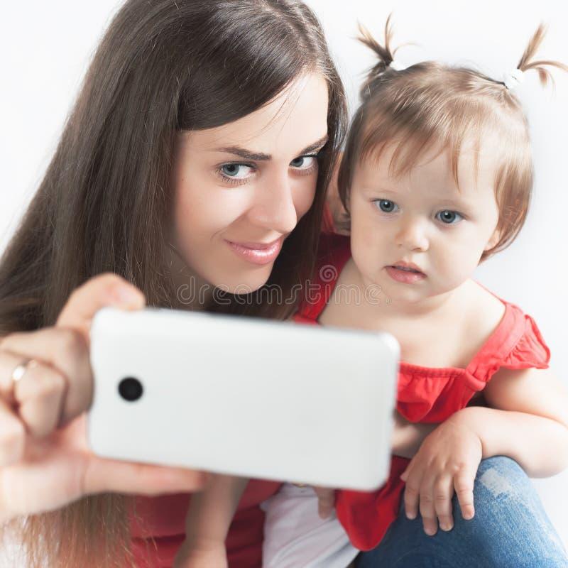 滑稽的婴孩和母亲在手机做selfie 库存照片