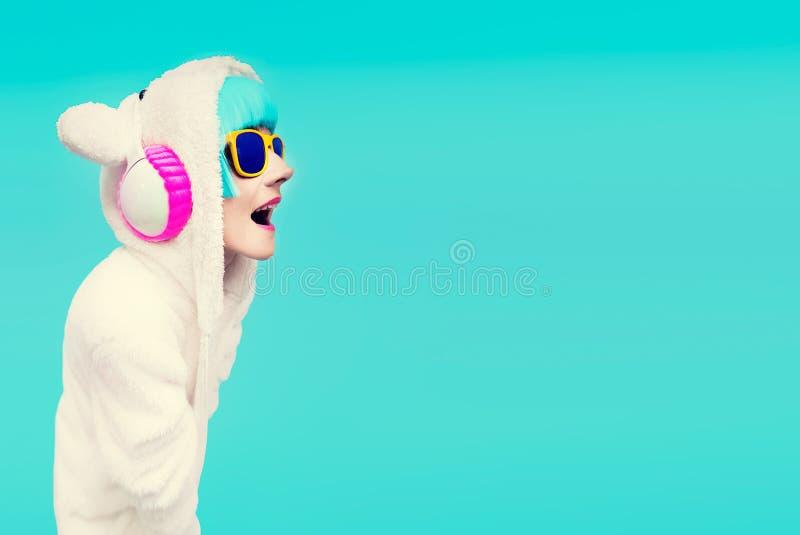 滑稽的DJ女孩运动衫玩具熊在蓝色背景中听 免版税库存照片