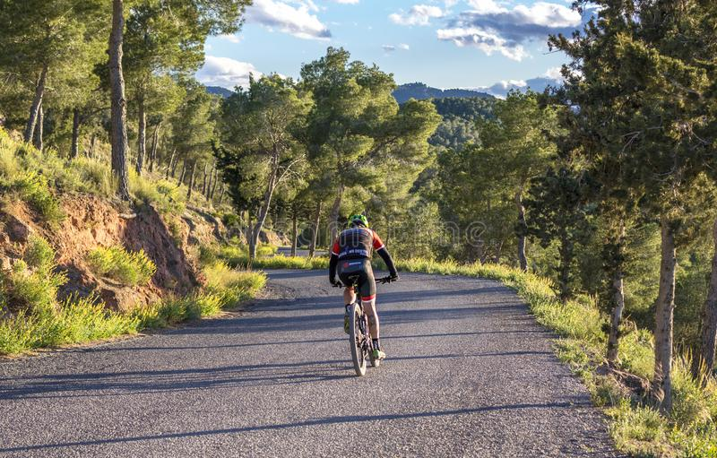 穆尔西亚,西班牙- 2019年4月9日:忍受在他凉快的自行车的赞成路骑自行车者困难的山上升 库存图片