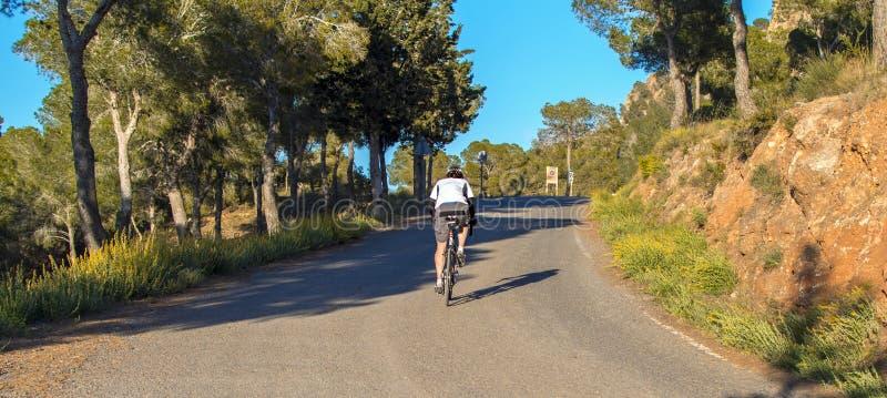 穆尔西亚,西班牙- 2019年4月9日:忍受在他凉快的自行车的赞成路骑自行车者困难的山上升 免版税库存照片