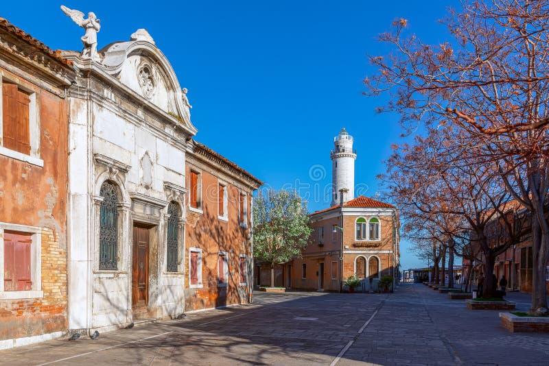 穆拉诺岛威尼斯,意大利- 2019年3月26日:一个小正方形的看法与老房子的在海岛穆拉诺岛和灯塔上 免版税库存图片