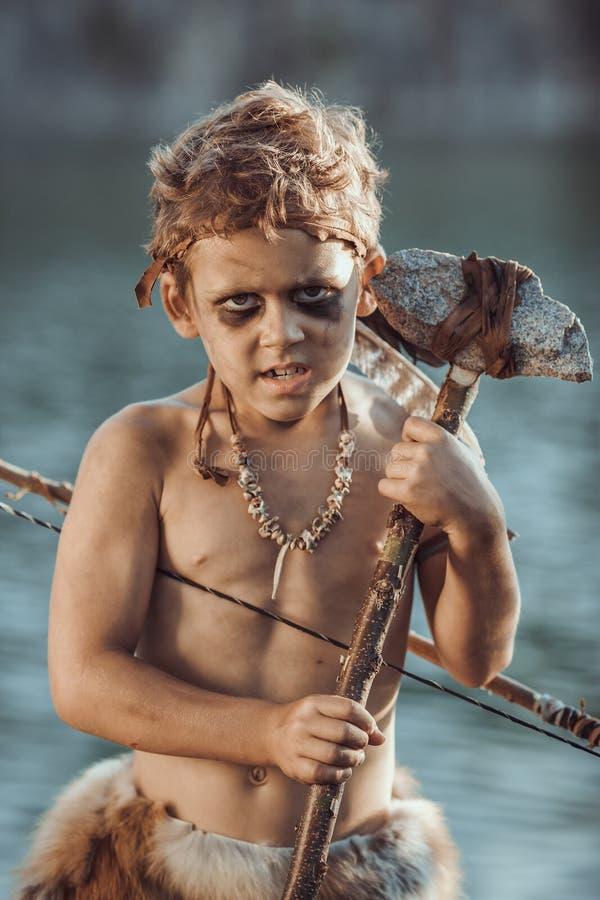 穴居人,有寻找原始的武器的男子气概的男孩户外 古老史前战士 英勇电影神色 免版税库存照片