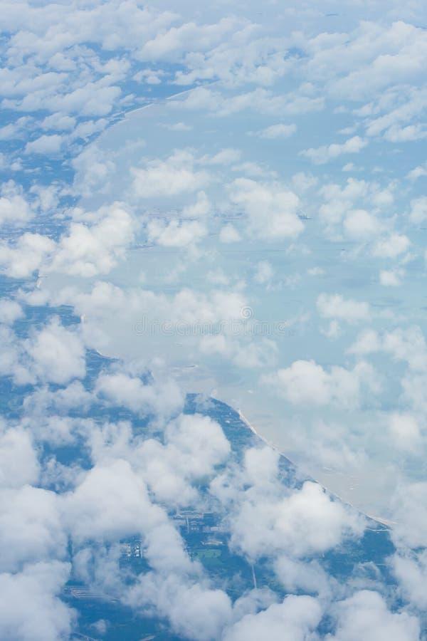 空中天空和抽象白色云彩从飞机窗口、海湾美丽的曲线和蓝色海背景 软的早晨光 免版税库存图片