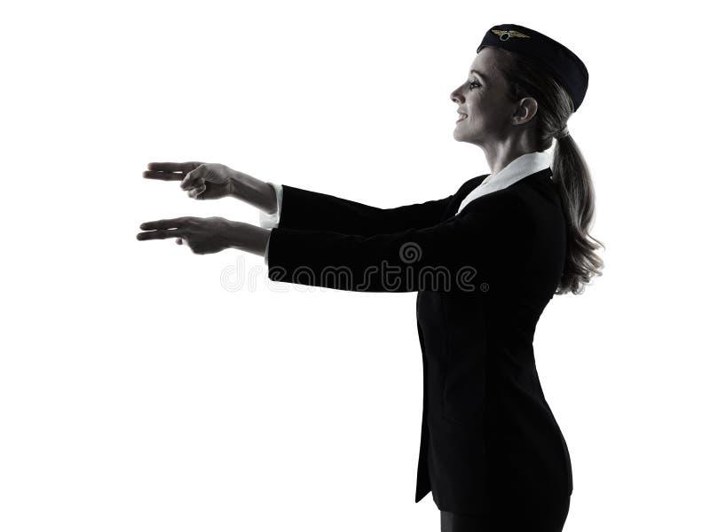 空中小姐客舱指向乘员组的妇女显示被隔绝的剪影 库存照片