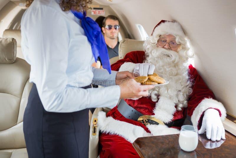 空中小姐对圣诞老人的服务曲奇饼在私人喷气式飞机 免版税库存图片