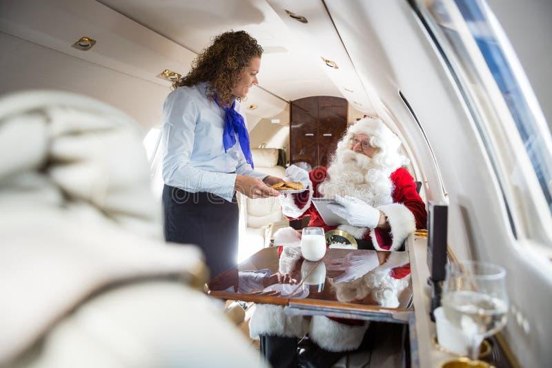 空中小姐对圣诞老人的服务曲奇饼在私人喷气式飞机 库存图片