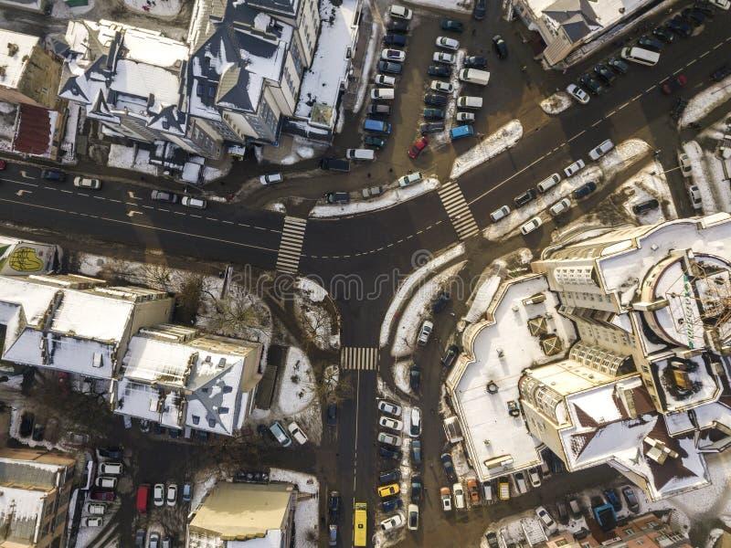 空中黑白现代城市冬天顶视图有高楼,停放的和移动的汽车的沿有路标的街道 免版税库存照片