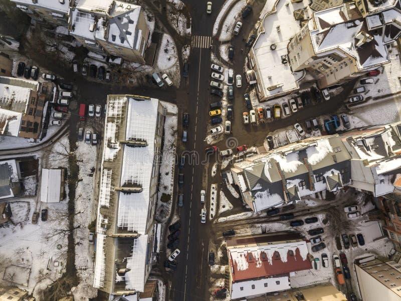空中黑白现代城市冬天顶视图有高楼,停放的和移动的汽车的沿有路标的街道 免版税图库摄影