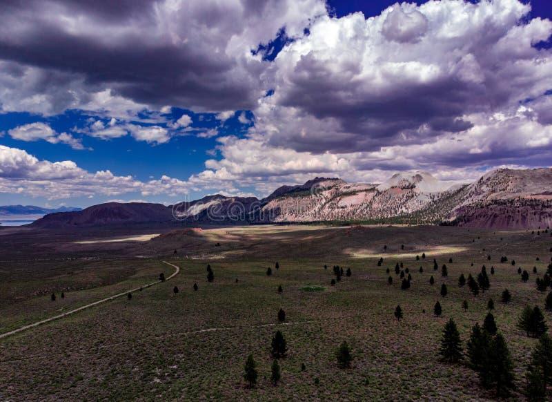 空中,白色云彩寄生虫视图在雪的加盖了内华达山东部山 库存照片
