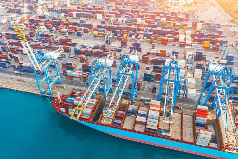 空中tope观看-有很多容器的重的巨大的船被停泊在口岸的码头,装载用起重机在工业 免版税图库摄影