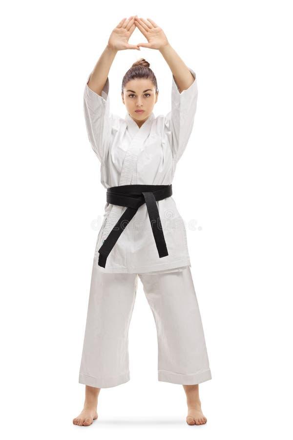 空手道和服实践的kata的年轻女人 免版税库存图片