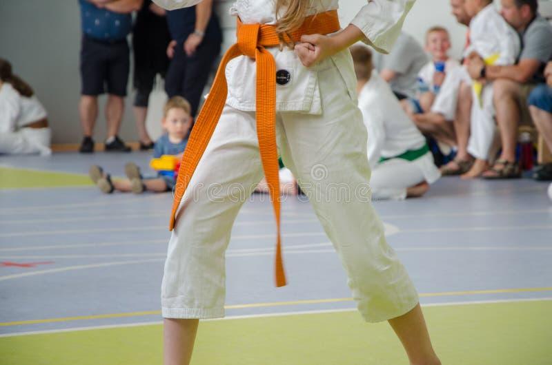 空手道竞争 和服的一个女孩有橙色传送带的 没有表面 库存照片