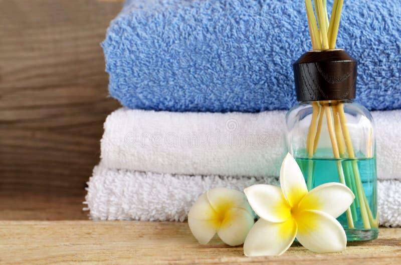 空气清新剂芳香棍子和堆在老木桌上的清洁毛巾在家 清除的疑虑自创芦苇分散器 免版税图库摄影