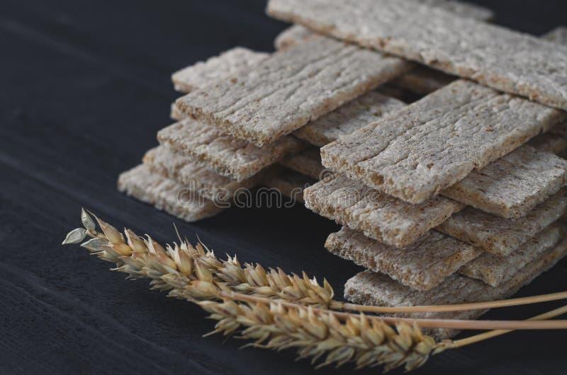 空气饮食大面包在黑暗的背景的一张木桌上说谎在麦子的耳朵旁边 库存照片