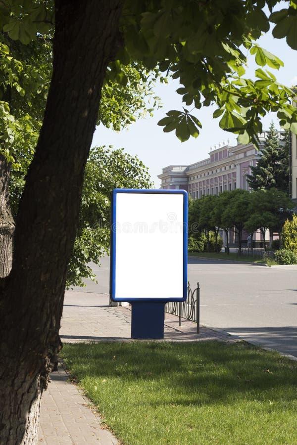 空白嘲笑在城市背景的垂直的街道海报广告牌 免版税库存照片