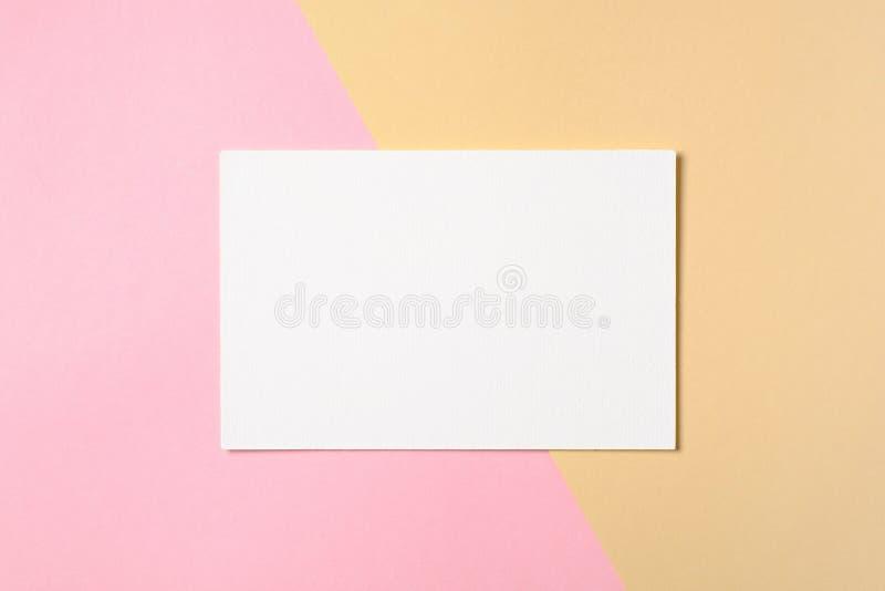 空白在两种颜色的粉红彩笔和黄色背景的白皮书卡片 平的位置,顶视图,在头顶上 创造性的布局,问候 库存照片