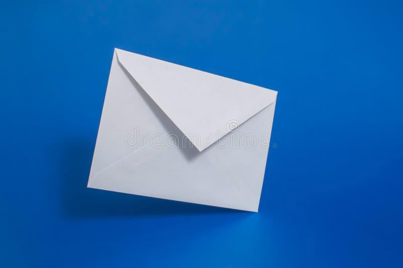 空白在蓝色背景的白皮书信封 免版税图库摄影