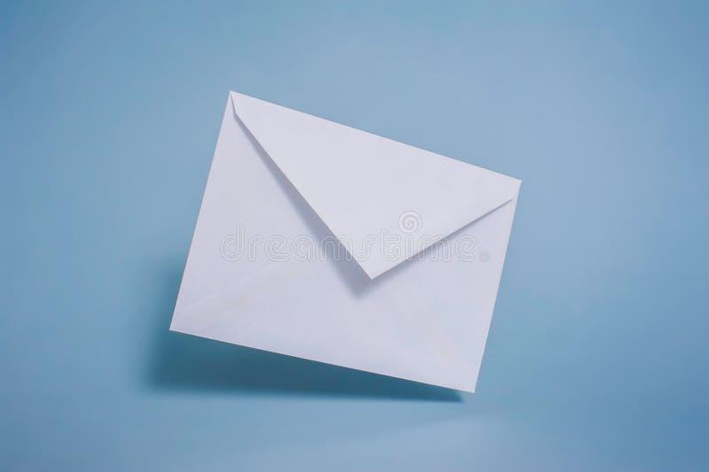 空白在蓝色背景的白皮书信封 库存图片