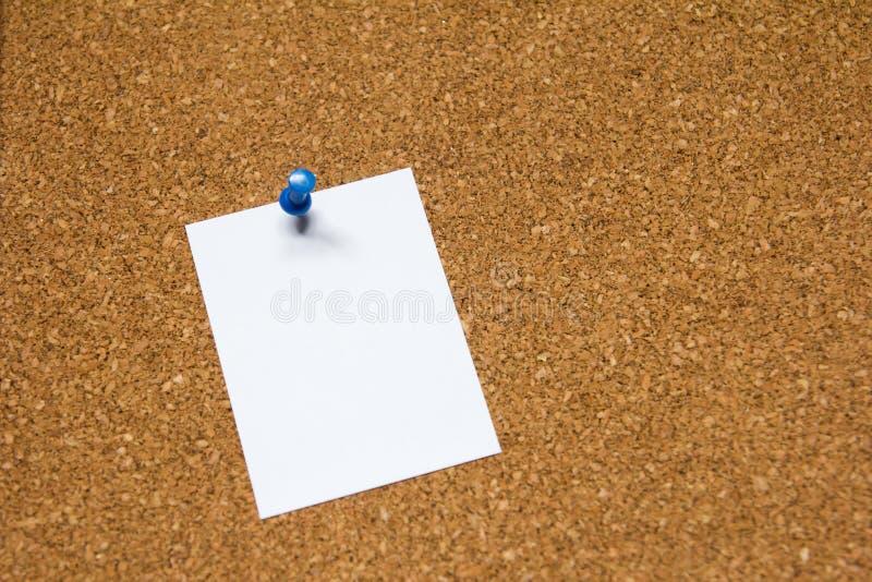空白在黄柏板背景的白皮书别针提醒的,做名单或新闻板 库存照片