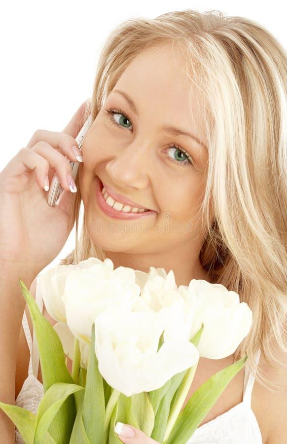 空白白肤金发的快乐的电话的郁金香 免版税库存照片