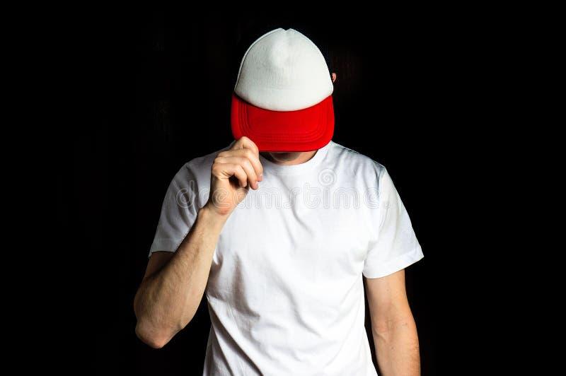 空白白色,红色棒球帽和白色T恤杉的人,在黑背景,嘲笑,自由空间,商标介绍 免版税库存照片