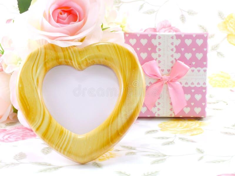 空白的与桃红色玫瑰和礼物盒的照片心脏木框架在甜花 免版税库存图片
