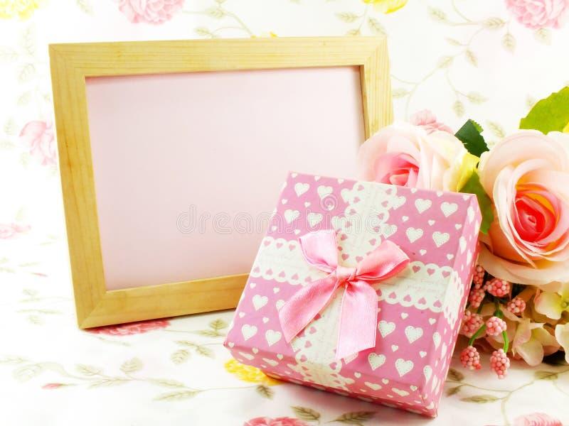 空白的与桃红色玫瑰和礼物盒的照片木框架装饰了花背景 免版税库存图片