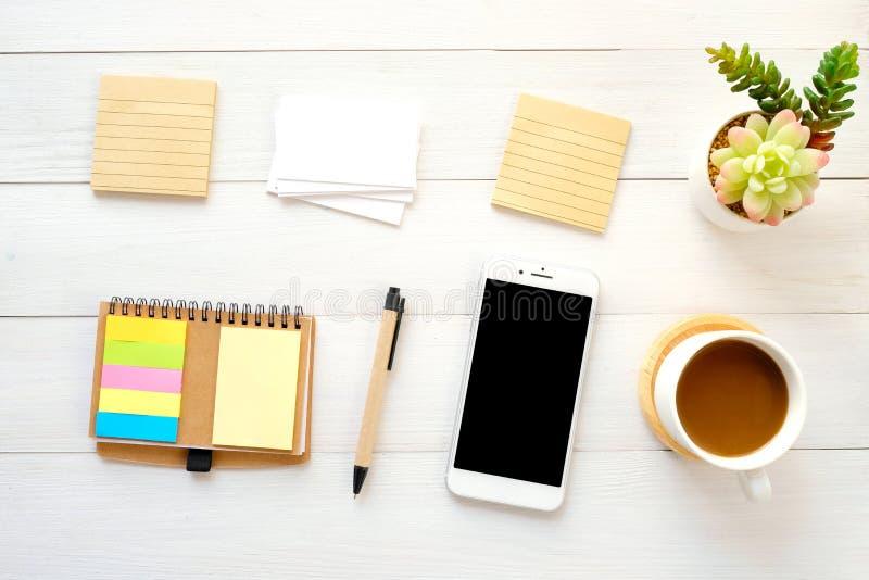 空白的便条纸、名片、智能手机、笔和咖啡在白色木桌背景,与拷贝空间文本的,顶视图 免版税库存照片