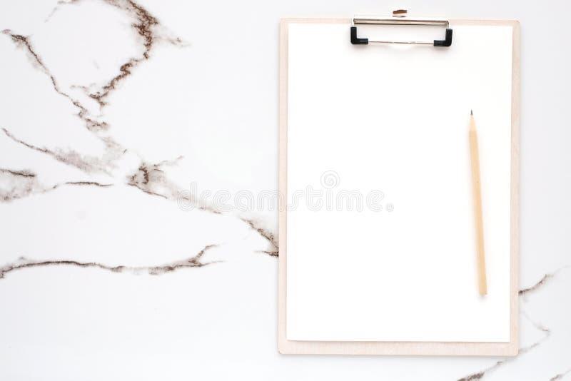 空白的便条纸和铅笔在剪贴板在白色大理石背景,与拷贝空间文本的,顶视图 免版税库存图片