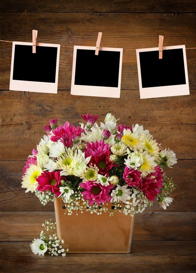 空白的偏正片照片构筑垂悬在与桃红色和白花夏天花束的一条绳索在木桌上的有木背景 免版税库存照片