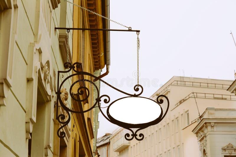 空白的卵形牌,垂悬从锻铁托架 免版税库存照片