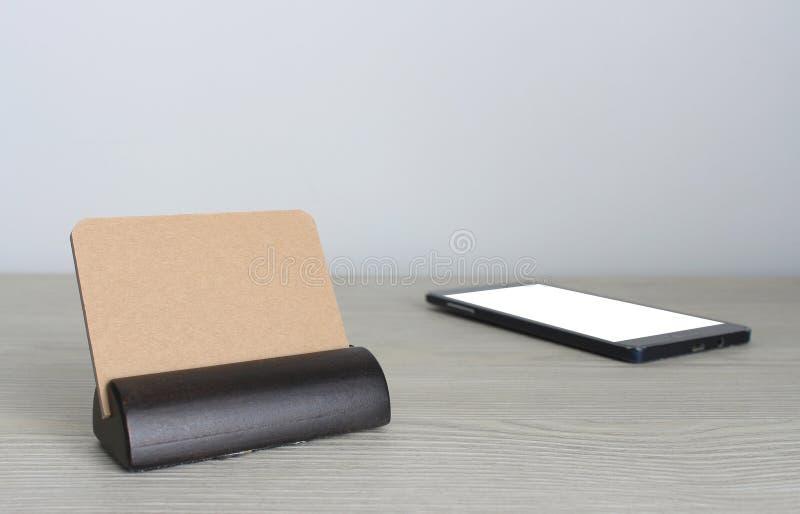 空白的名片和智能手机在木办公室桌上与 图库摄影