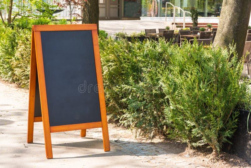 空白的咖啡馆黑板户外边路灌木城市都市Restau 库存图片