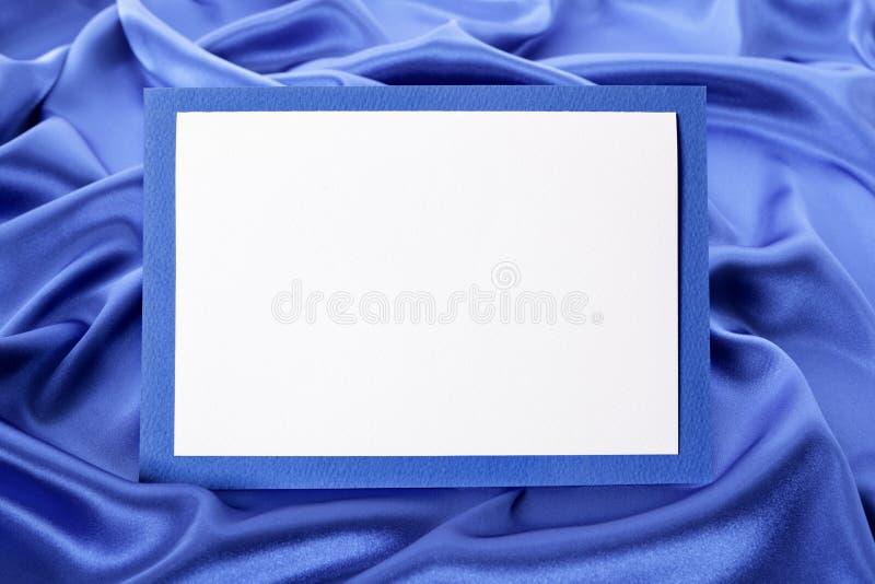 空白的圣诞节或生日贺卡或邀请有蓝色缎背景,拷贝空间 库存图片