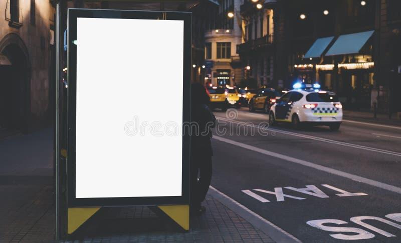 空白的在公共汽车站,空的广告广告牌大模型的广告灯箱在夜班车驻地,在背景城市的模板横幅的 免版税库存照片