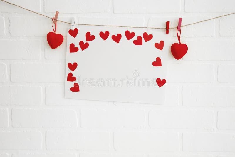 空白的在白色砖墙上的心脏纸框架 库存照片
