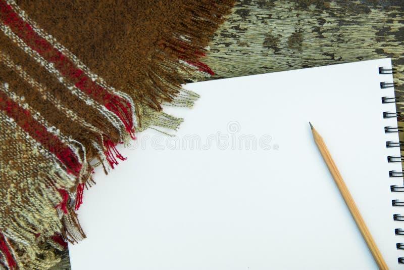空白的在被风化的木长凳的写生簿铅笔方格的棕色红色灰色格子花呢披肩在公园 艺术略图创造性概念 免版税库存图片