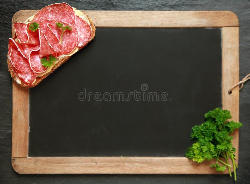 空白的学校板岩用蒜味咸腊肠三明治 库存图片