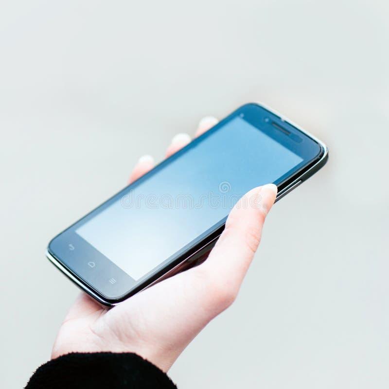空白的宽银幕智能手机在妇女的手上 库存图片