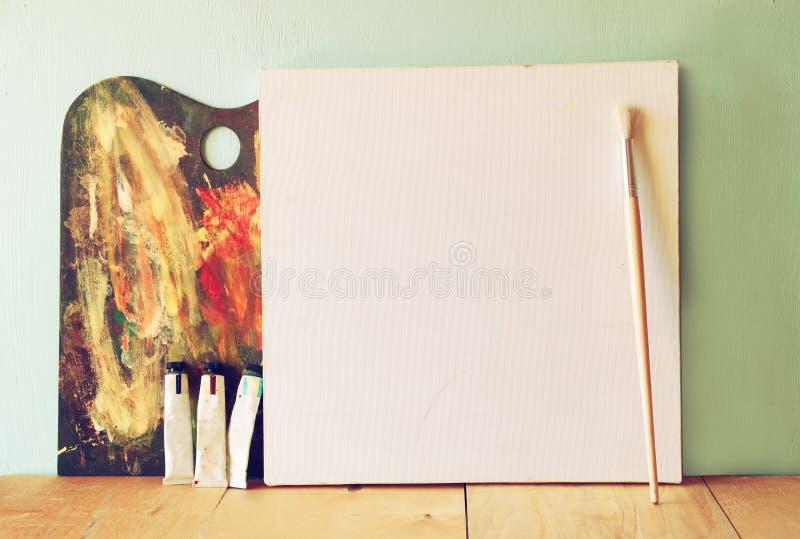 空白的帆布或海报与木调色板在木桌和织地不很细背景上 库存图片