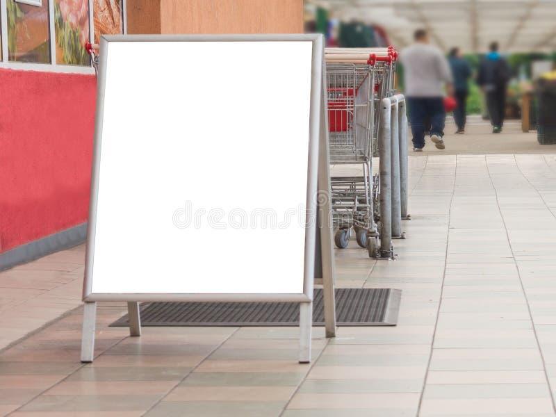 空白的广告牌在一个超级市场,在手推车旁边 库存图片