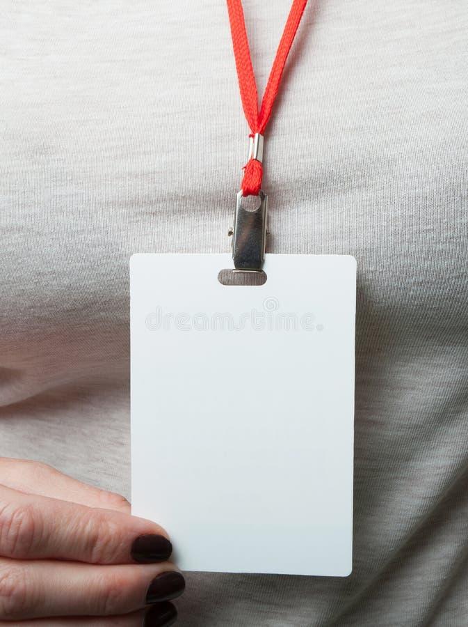 空白的徽章大模型在灰色衣裳背景的妇女的手上  垂悬的简单的空的名牌嘲笑在与红色的脖子 免版税图库摄影