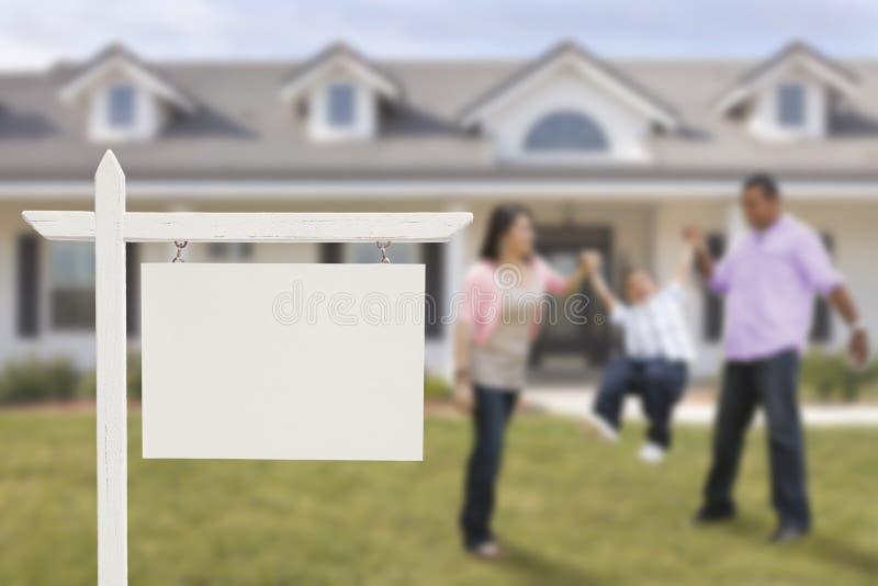 空白的房地产标志和拉美裔家庭在议院前面 库存照片